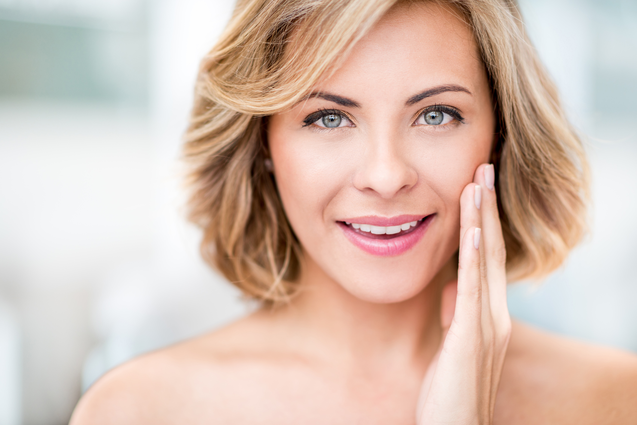 Beauty portrait of a woman stroking her skin