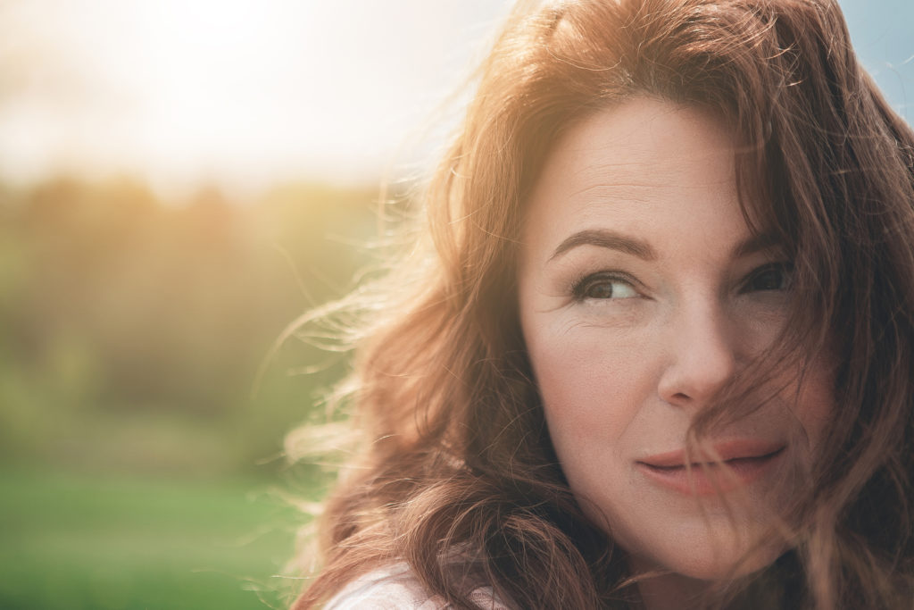 Natural beauty. Close up portrait of dreamful woman with red curly hair. She is looking aside with enjoyment and smiling while resting in the fresh air. Copy space