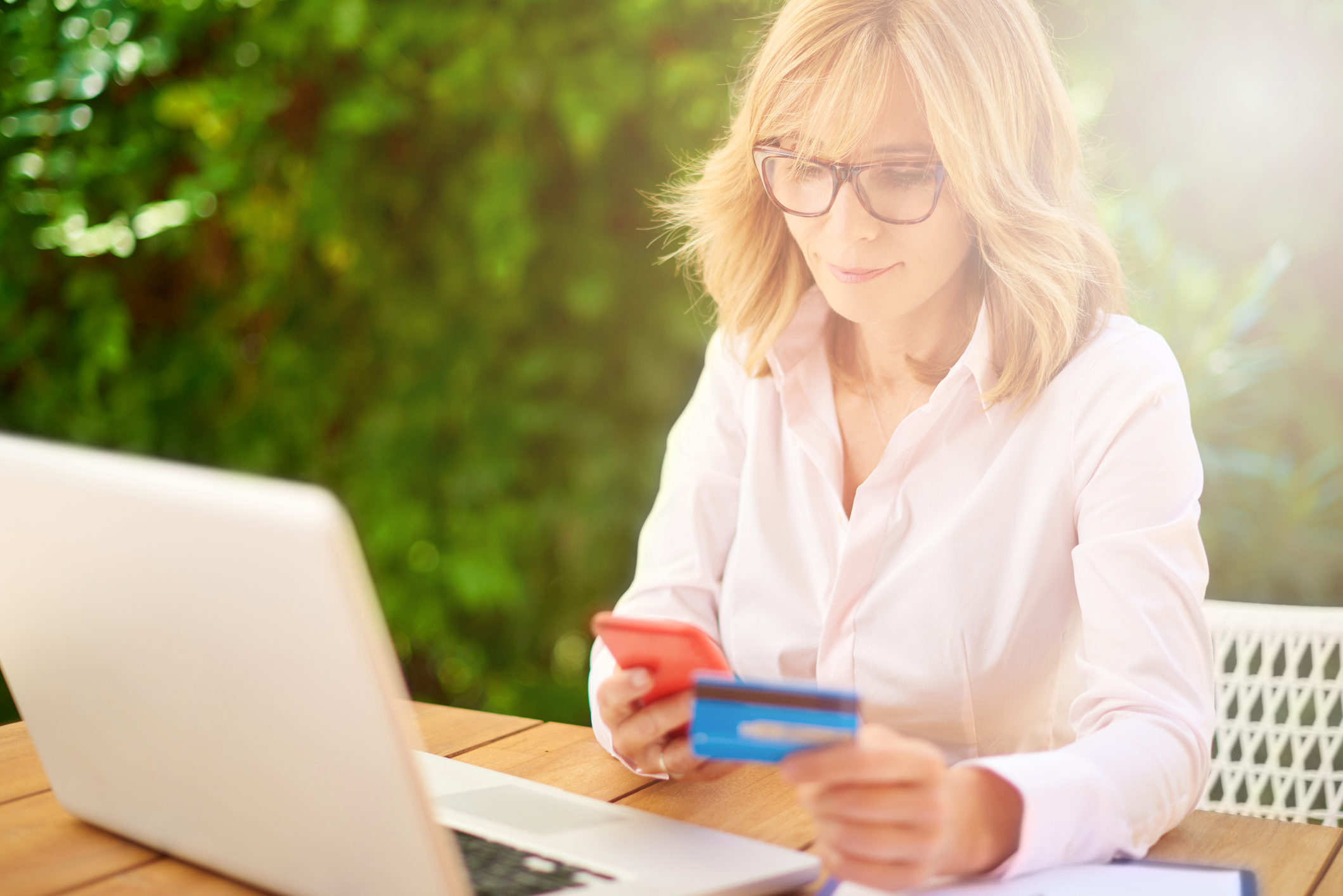 High angle shot of attractive middle aged woman shopping with credit card and using laptop while sitting in the garden at home.
