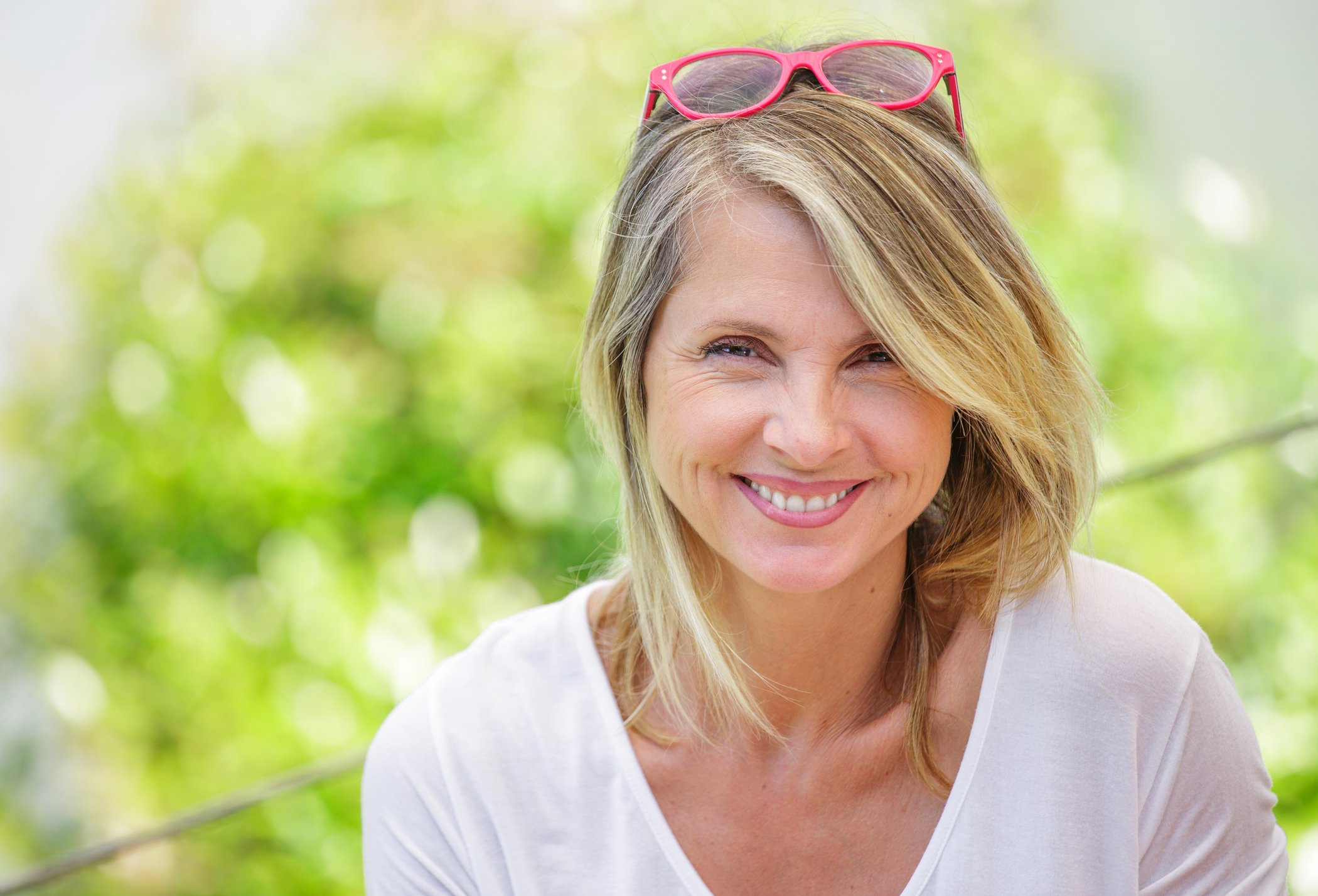 Portrait of charming blond woman of middle-aged smiling in glasses