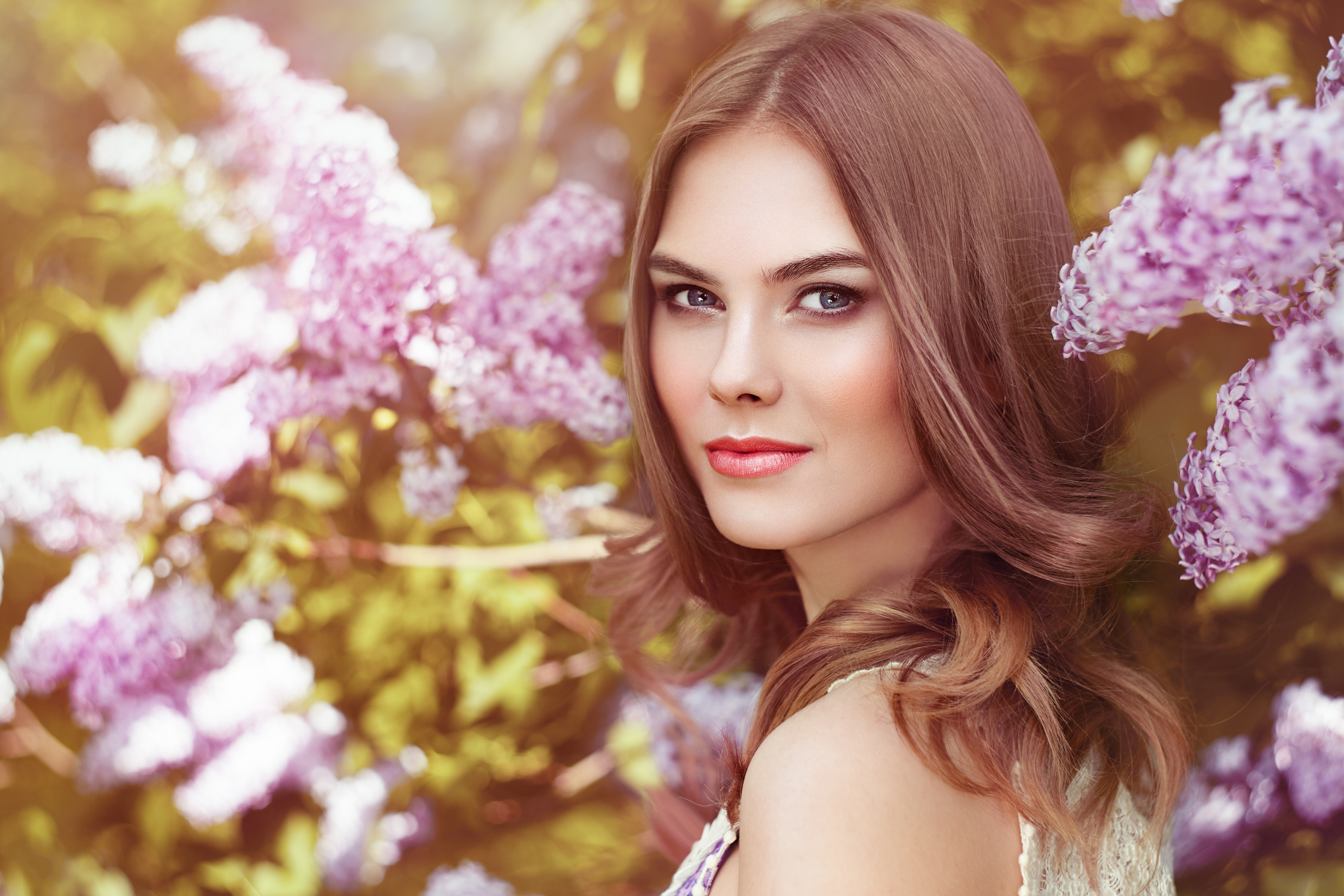Beautiful Woman with Flowers of Lilac. Spring Blossom. Sexy Glamour Summer Beautiful Lady with Healthy and Beauty Hair